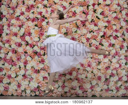 Portrait of a beautiful blonde little girl in white gown. Ballerina on a background of a flower wall in the studio