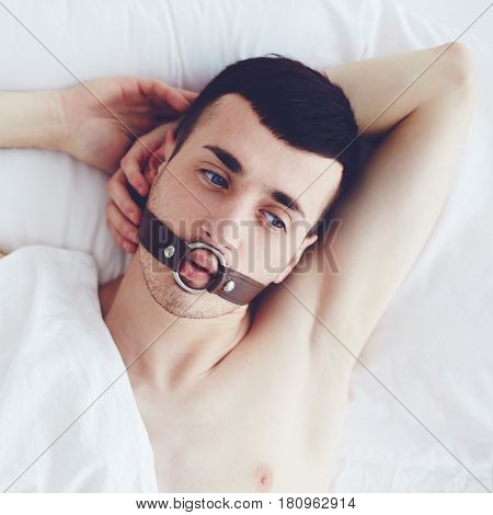 Handsome Man With A Face Strap Laying In Bed