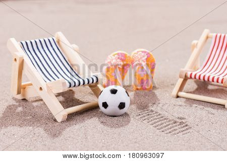 Two empty sun loungers with ball and shoes on the beach
