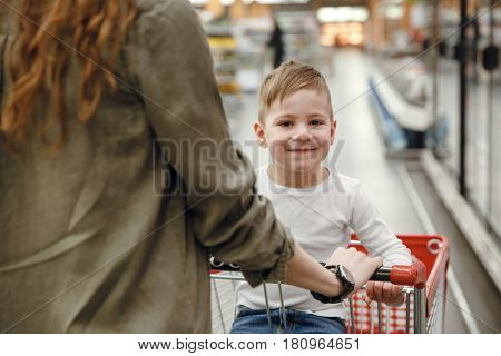 View from back of mather with son which sitting in shopping trolley  and looking at the camera in the supermarket