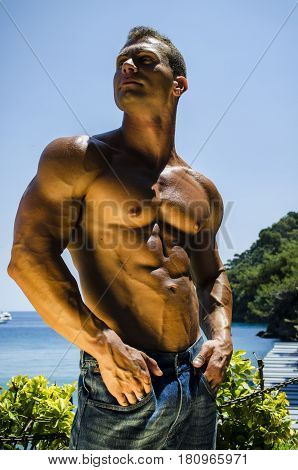 Handsome young muscle man at the seaside, outdoors, showing muscular pecs and torso in front of the sea