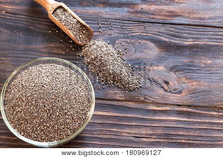 Glass bowl of chia seeds on the wooden background