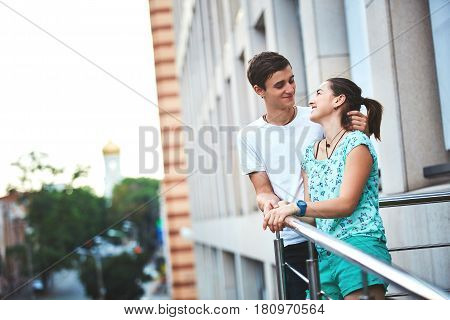 Young people, couple having date on the street. A loving couple on a date on a summer evening. The guy with the girl hugs and kisses. Youth, first feelings, first love, first dates. The girl jumps the guy on the back