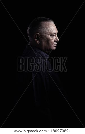 Classic profile portrait of aged man wearing shirt against black background - retirement concept