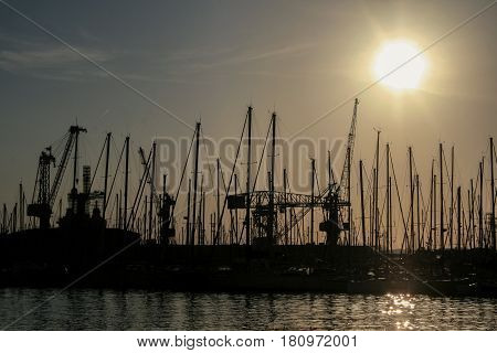 Shape of boat masts and cranes at sunset in Toulon port France