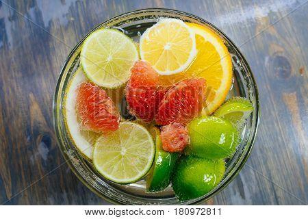 Citrus in water with bubbles in transparent plate Oranges, lemons, greyfrut, Pamela lemonade