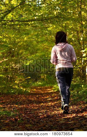 Woman Walking Cross Country Trail In Autumn Forest