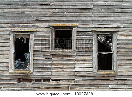 Three Broken Windows in a Dilapidated Brown Wooden House