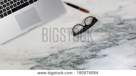 Flat lay of a partial laptop pen and reading glasses on natural marble desktop