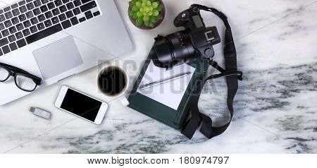 Flat lay of a partial laptop camera baby plant pen reading glasses smartphone thumb drive and coffee on natural marble desktop