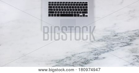 Flat lay of a partial laptop on natural marble desktop