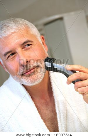 Senior man in bathroom with electric razor