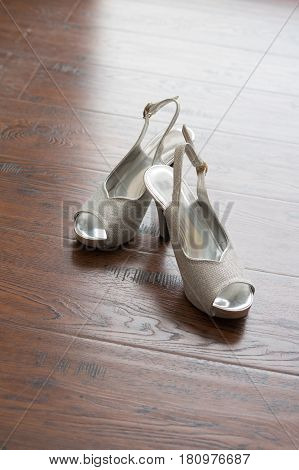 Women's wedding shoes lying on the wood wooden floor. Bride's morning wedding preparation concept