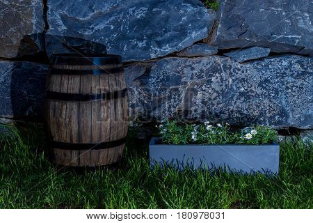 Night Shot Of A Vintage Oak Barrel On The Lawn Beside A Pot Of Daisy Flowers With Natural Stone Wall