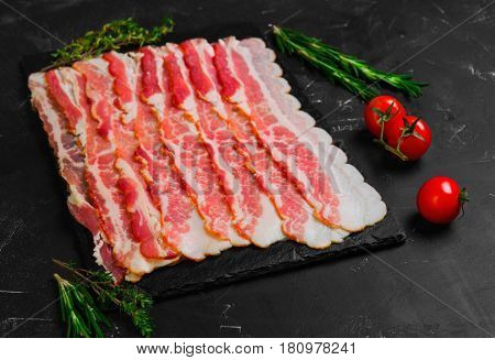 Raw sliced bacon ready for cooking on dark black concrete background. Ingredients for raw bacon cherry tomatoes thyme rosemary.