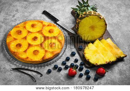 Homemade fruit pineapple pie cake. Ingredients for pineapple blueberry pie cake strawberry fresh cut into pieces of pineapple vanilla. Gray concrete background.