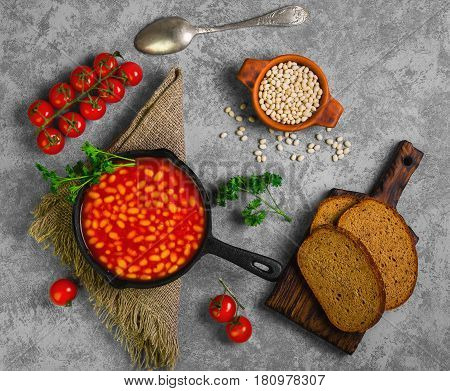 Baked stewed white beans in a cast-iron frying pan in tomato sauce. Ingredients for stewed beans are tomatoes parsley raw beans rye bread burlap spoon. Gray concrete background. Top view from above and copy space.