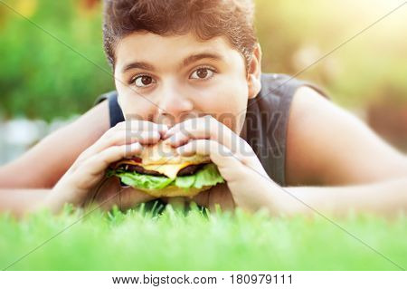 Portrait of a teen boy lying down on the grass on bright sunny day and with pleasure eating tasty burger, happy time in summer camp