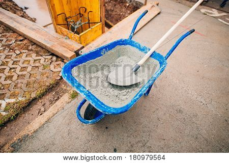 Blue clean new wheelbarrow for cement. Laying the first shovel cement in the foundation on the construction of the house.