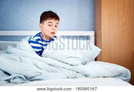 Sleepy boy sitting in bed. Tired child in bedroom
