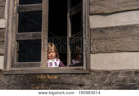 Small and lonely caucasian baby girl or toddler looking out of old wooden cabin window to suggest poverty or recession