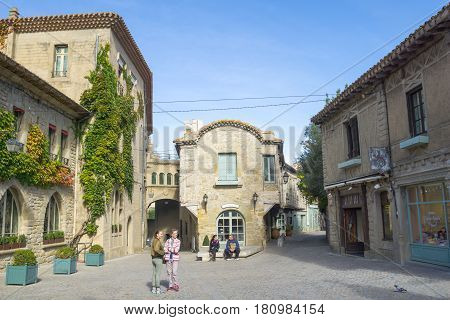Carcassonne, France - October 21, 2016; Tourists in street bordered by traditional style stone buildings and shops in historic city of Carcassonne France