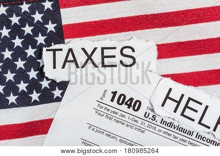 Taxes and Help on torn paper lay on a 1040 tax form on top of American flag