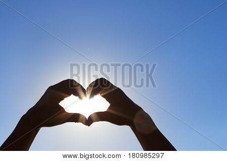 Silhouette of wet hands in heart shape with sun in the middle