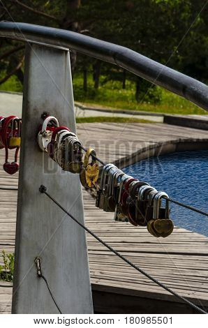 the small locks suspended on the bridge at a reservoir for the long relations