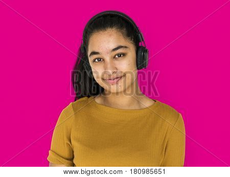 Indian girl smiling and listening music by headphones