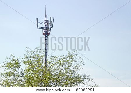 Mobile phone communication tower transmission signal with blue sky background and tree