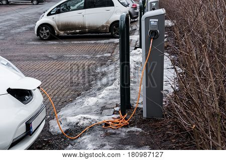 Charging an electric car station with the power cable supply plugged-in station in public park