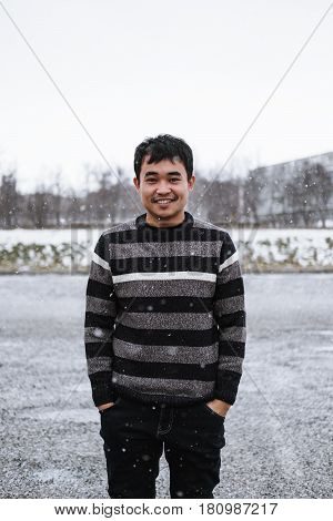 a man in sweater standing in snowy day in winter, with smiling face