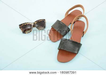 female shoes with sunglasses on light blue background