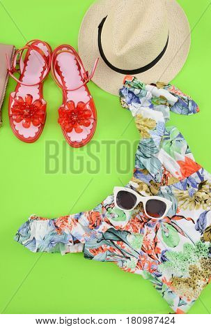 Fashion. Summer woman accessories-Summer floral clothes, ,hat, shoes green background
