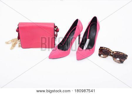 Fashion concept. Pink handbag , shoes ,sunglasseson a white background