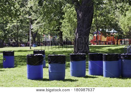 Montreal, Quebec - July 27, 2016 - Wide view of blue utility bins lined up across the grass in a park in Montreal, Quebec on a sunny day in late July.