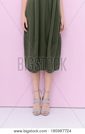 Woman in sundress . high heels. Perfect female legs -light pink background