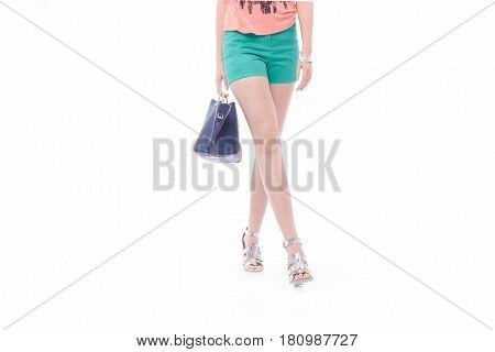 Woman long sexy legs wearing short blue shorts with handbag walking