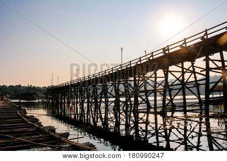 Saphan Mon (Mon Bridge) the large old wooden bridge across Song Karia river to the village reflecting with water located in Sangklaburi District Kanchanaburi Thailand