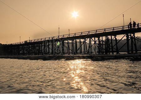Saphan Mon (Mon Bridge) the large old wooden bridge across Song Karia river to the village in the evening located in Sangklaburi District Kanchanaburi Thailand
