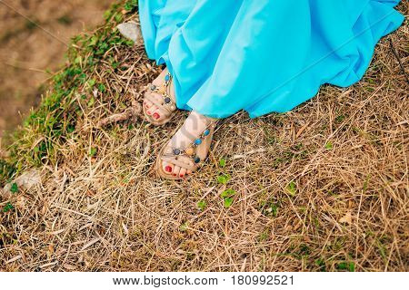 Female feet in sandals. On dry grass. A girl in a blue sarafan.