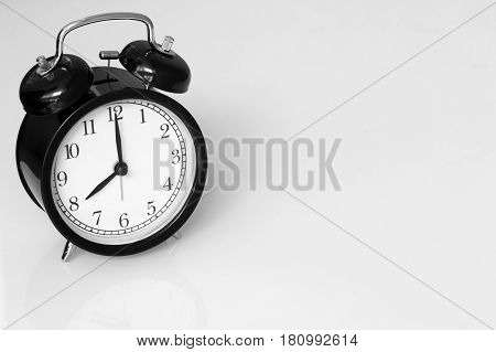 clock retro at 8 o'clock on white table background with space for text.