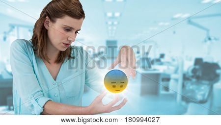 Digital composite of Woman sitting with emoji and flare between hands against blurry blue office