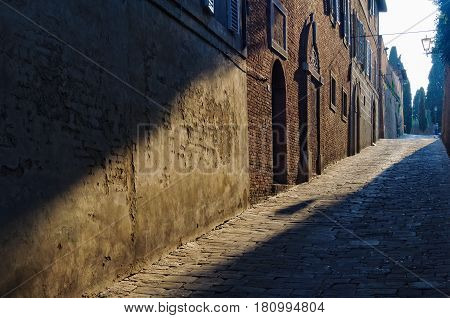 Ray of sunshine lights the brick walls and cobblestone in Vicolo di San Clemente - Siena, Italy