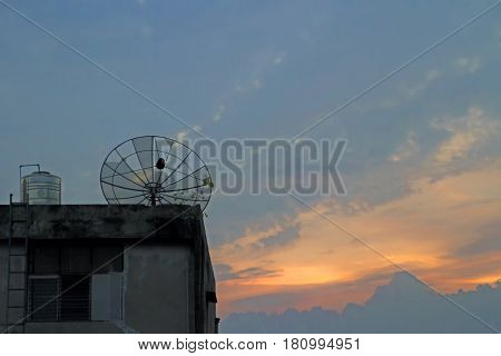 Satellite old dish on rooftop on evening