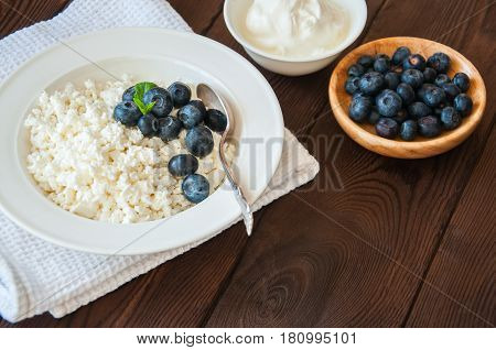 Organic Farming Cottage Cheese In A White Plate Sour Cream And Blueberries On A Wooden Background. C