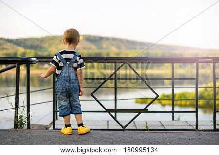 The boy stands on the edge of the ledge. The child walks along the alley off the coast. The railing closes the passage to the stairs. Cliff above the river beyond the fence.