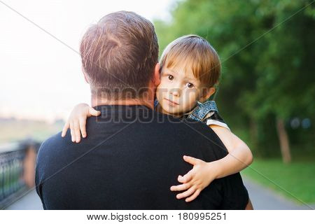 The son hugs his father. The child is in the hands of his father the boy holds the parents by the shoulders. Family walk along the alley. Good feelings in relationships love and care.