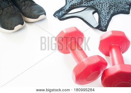 Closeup of red dumbbells with sneaker shoes and sport bra Sport equipments on white background